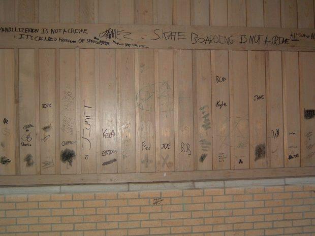 Photographie d'un mur en bois et en brique avec des graffiti à l'encre noire.