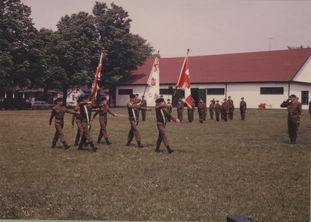 Photographie en couleur montrent des garçons en uniforme défilant avec des drapeaux , derrière un parc avec des arbres et un bâtiment blanc au toit rouge.