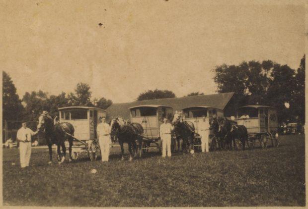 Une photo sépia des années 30 montre 4 hommes vêtus de blanc dans un parc,  A leur droite, un cheval tirant une carriole.  L'homme à gauche semble avoir quelque chose à la main.  Il y a un cinquième homme dans une carriole à l'extrême droite.  Au fond, on distingue un grand toit et la clôture d'un terrain de baseball.