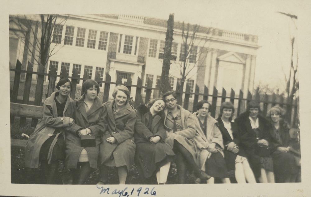Une photo sépia datant de 1926 montre 9 filles assises sur un banc, une clôture en bois derrière elles et un grand bâtiment de deux étages au fond.  La photo a été prise de biais, la clôture et le bâtiment semblent pencher vers la droite.