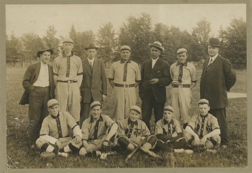 Image sépia de sept hommes debout et cinq assis devant, posant pour une photo de l'équipe.  Ils sont dans un parc et huit d'entre eux portent un uniforme