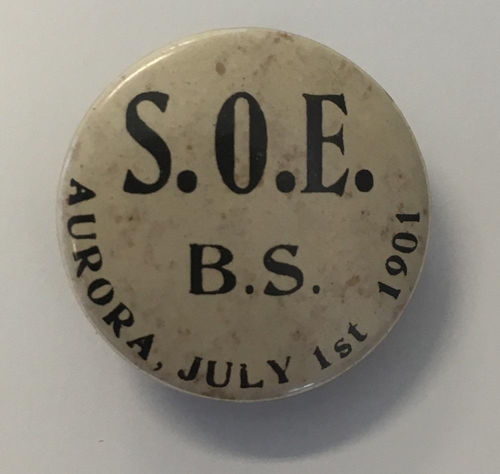 Petit bouton circulaire sur un fond beige/brun avec texte en noir.