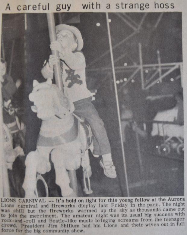 On voit une coupure de journal avec une  photo en noir et blanc montrant un petit garçon monté sur un cheval de manège, il porte un chapeau et regarde le ciel, au fond , un landau, des gens et une grande roue.