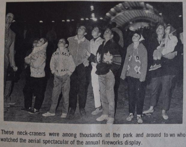Une coupure de journal montre une photo en noir et blanc de personnes regardant le ciel nocturne, avec au fond une scène éclairée, légende en bas.