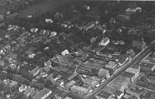 Une image aérienne en noir et blanc montre six pâtés de maison.  On y voit plusieurs bâtiments publics et résidentiels ainsi qu'un parc dans le coin supérieur gauche.