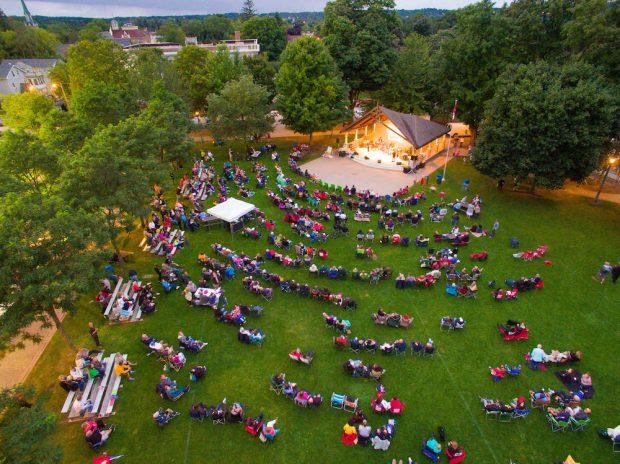 Photo en couleur prise par un drone montrant une section du parc bordée de grands arbres.  Les gens sont assis sur une grande pelouse regardant les musiciens jouant sur une grande scène éclairée.