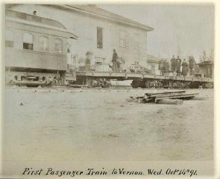 Photo en noir et blanc montrant une partie du wagon passagers d'un train et une plateforme où se tiennent des personnes, avec un édifice en arrière-plan.