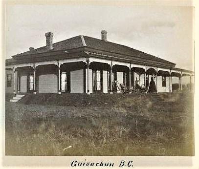 Photo en noir et blanc représentant la façade et le côté d'une maison à étage entourée d'une véranda. Une femme, debout sur la véranda, fait un signe de la main.
