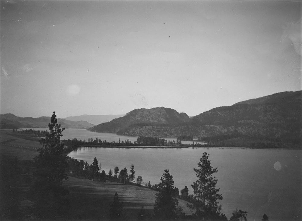Photo en noir et blanc représentant deux lacs et un isthme étroit avec des coteaux au loin.