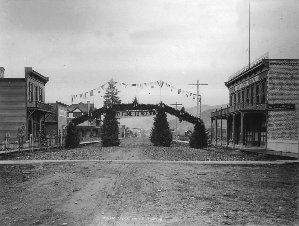 Photo en noir et blanc montrant une allée de gravier avec des édifices commerciaux de part et d'autre. En travers de la route, on voit une guirlande de branches de conifère arborant le mot « Bienvenue ».
