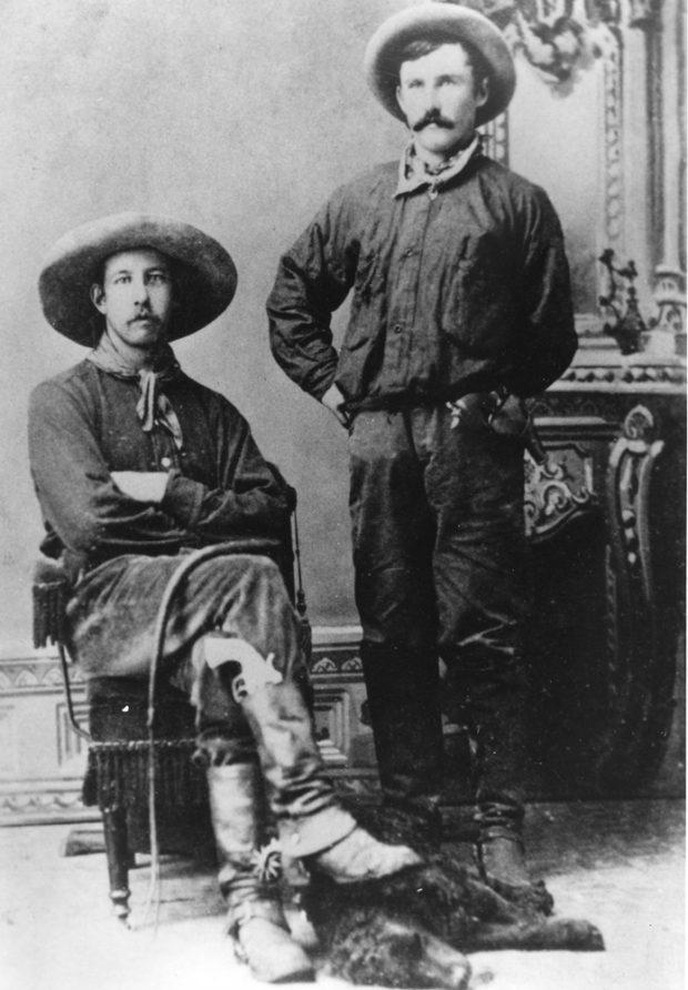Photo en noir et blanc de deux hommes en tenues et chapeaux de cowboy. L'un d'eux est assis, l'autre debout.