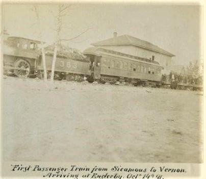 Photo en noir et blanc d'un train, avec la locomotive, une voiture de passagers et un édifice en arrière-plan.
