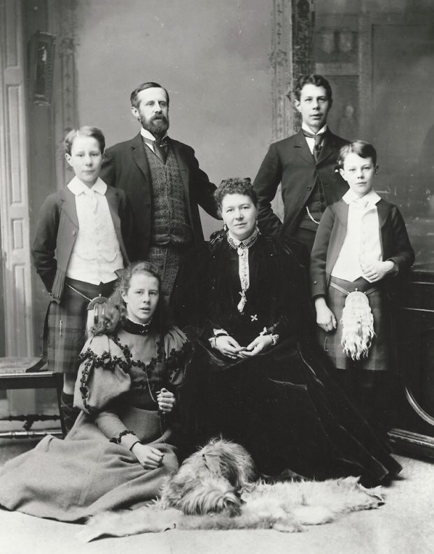 Photo formelle en noir et blanc représentant une famille de l'époque victorienne avec un homme, une femme, quatre enfants et un chien. Deux des garçons portent un kilt.