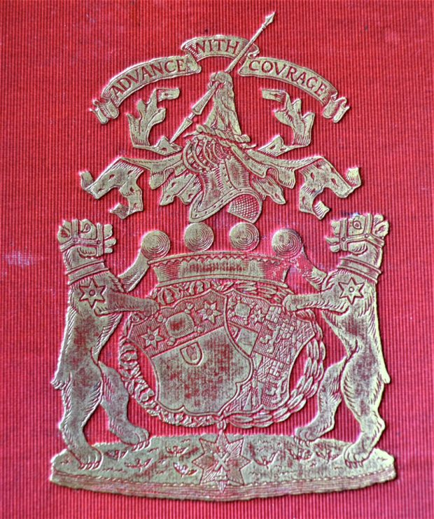 Armoiries de famille argentées sur fond rouge composées de deux lions flanquant des boucliers avec la devise « Advance with Courage » (avancer avec courage) au-dessus.