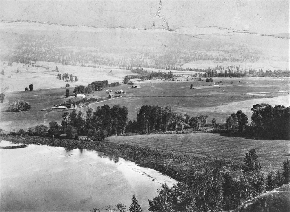 Photo en noir et blanc montrant les bâtiments d'une ferme et des arbres dans le lointain, et un lac dans l'angle inférieur gauche.