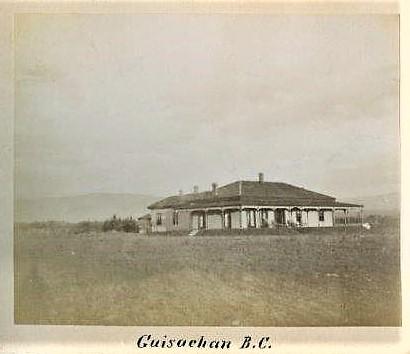 Photo en noir et blanc montrant la façade et le côté d'une maison à étage entourée d'une véranda avec un champ devant.