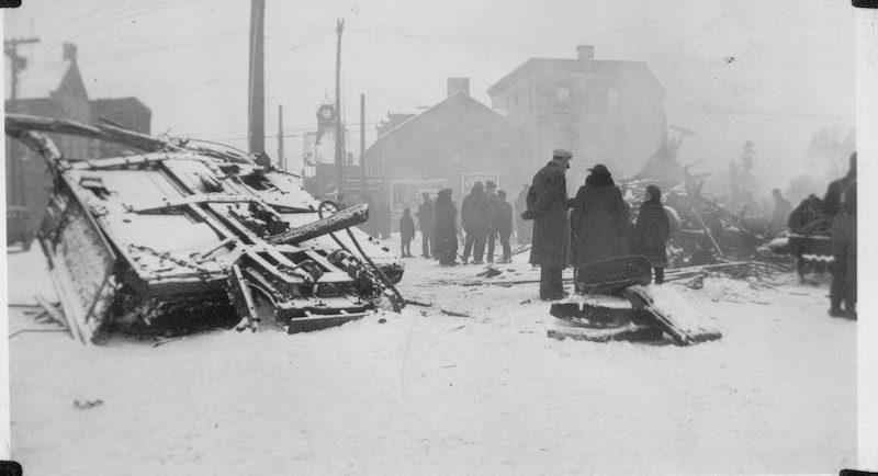 Photographie des décombres de la troisième voiture du train local de la vallée de l'Outaouais, à Almonte; on voit des gens qui marchent dans la ville, 1942