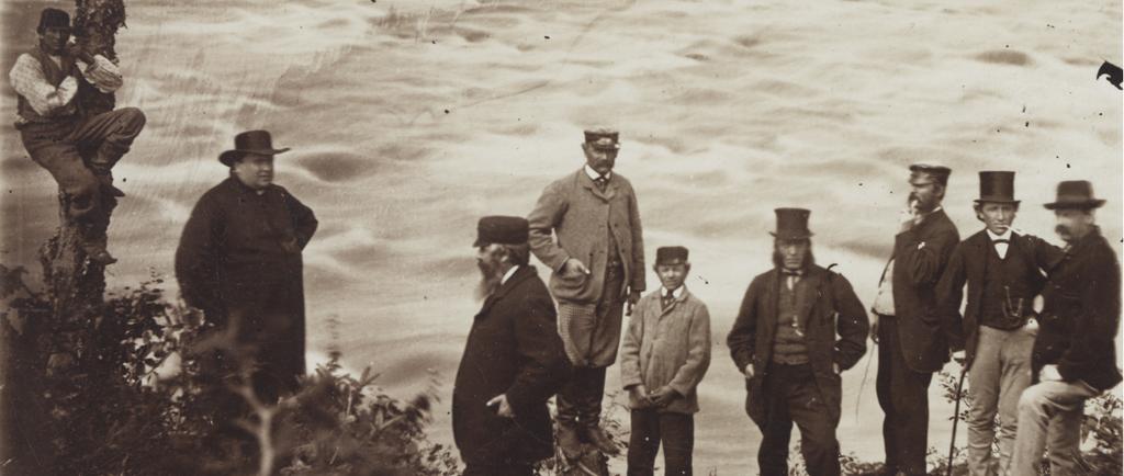 Photographie noir et blanc d'un groupe de neuf personnes sur la rive d'un cours d'eau tumultueux. À gauche, un homme est suspendu au tronc d'un arbre. Le curé Labelle, homme corpulent, porte une soutane et un chapeau de feutre à large bord. Au centre et à droite, six hommes et un adolescent en habit trois-pièces portant des chapeaux hauts de forme, casquettes ou chapeaux de feutre. Deux d'entre eux fument la pipe.