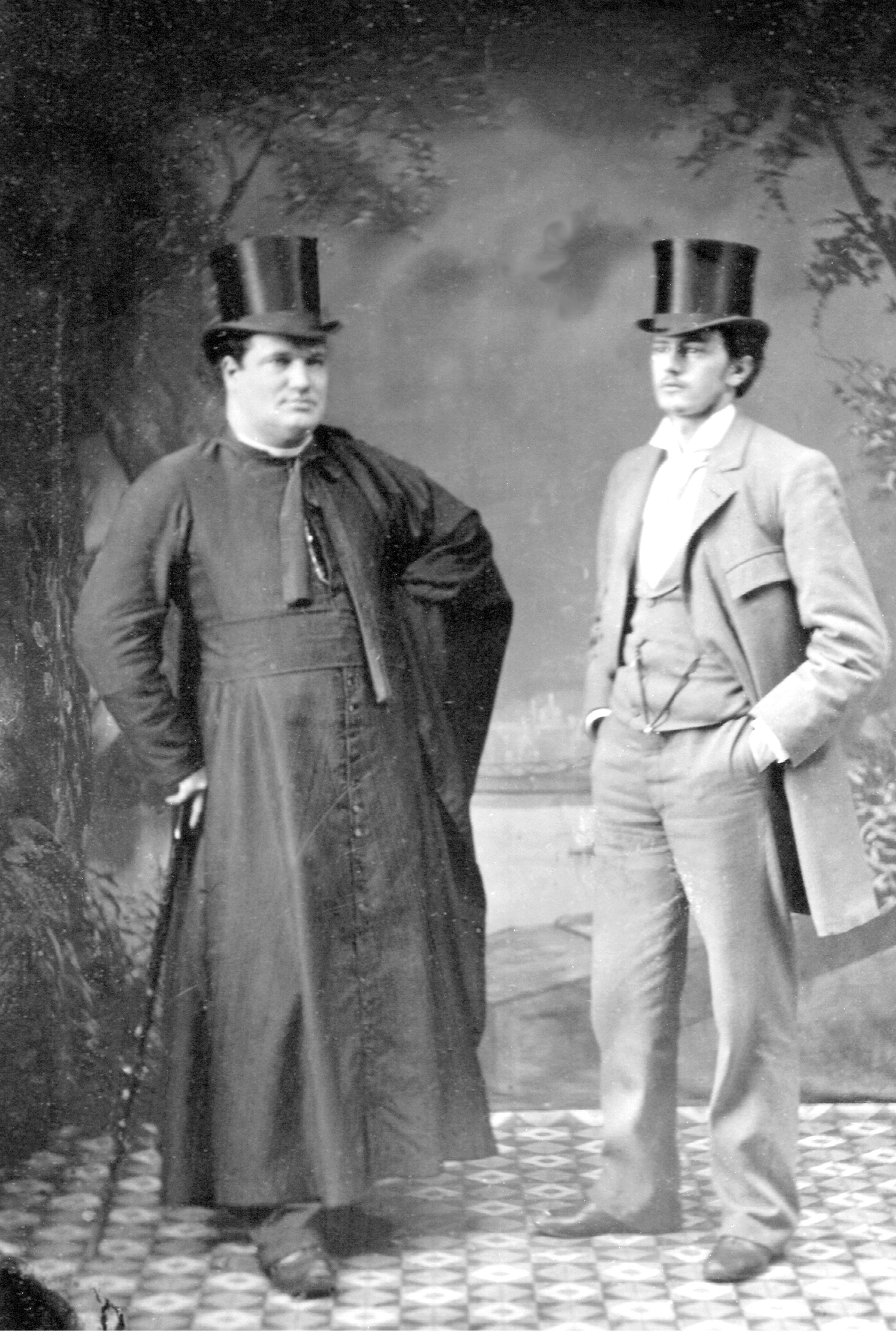 Image en noir et blanc de deux hommes se tenant debout dans un studio de photographie. L'un d'eux, un prêtre, est vêtu d'une soutane noire et s'appuie sur une canne à pommeau. L'autre homme porte un habit trois-pièces de couleur claire, ses mains sont dans les poches de son pantalon. Les deux hommes portent le chapeau haut de forme.