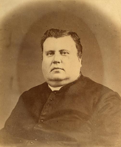Photographie sépia d'un prêtre dans la quarantaine. Le portrait montre la partie supérieure de son corps. L'homme bien en chair, il a un double menton, porte une soutane et un col romain.