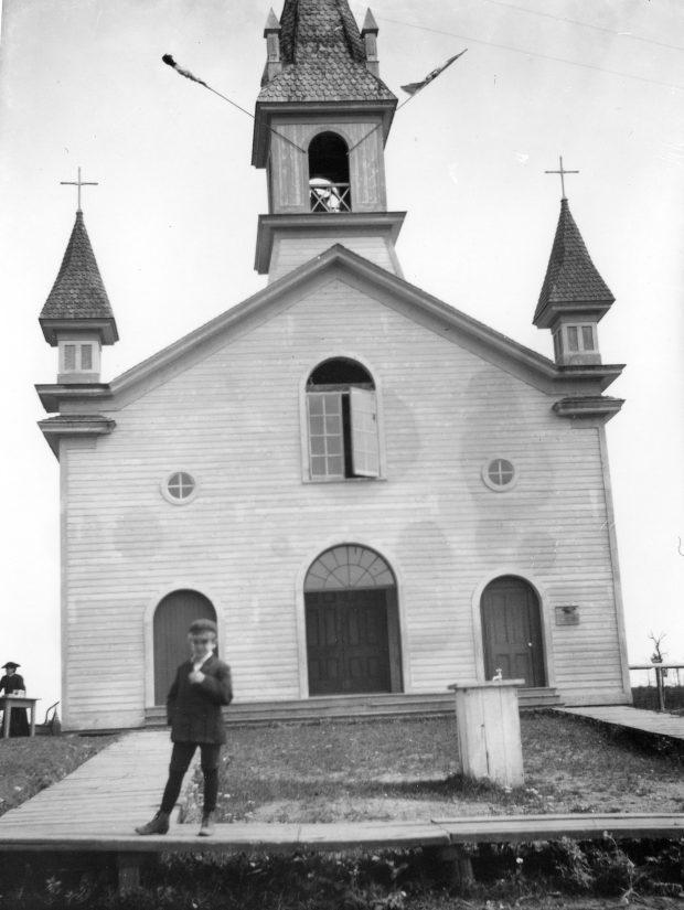 Photographie noir et blanc de la façade d'une petite église. Le bâtiment, dont le revêtement est en planches de bois, a trois portes, trois fenêtres au-dessus des portes et un clocher. Un jeune garçon se tient debout devant l'église sur le trottoir de bois.