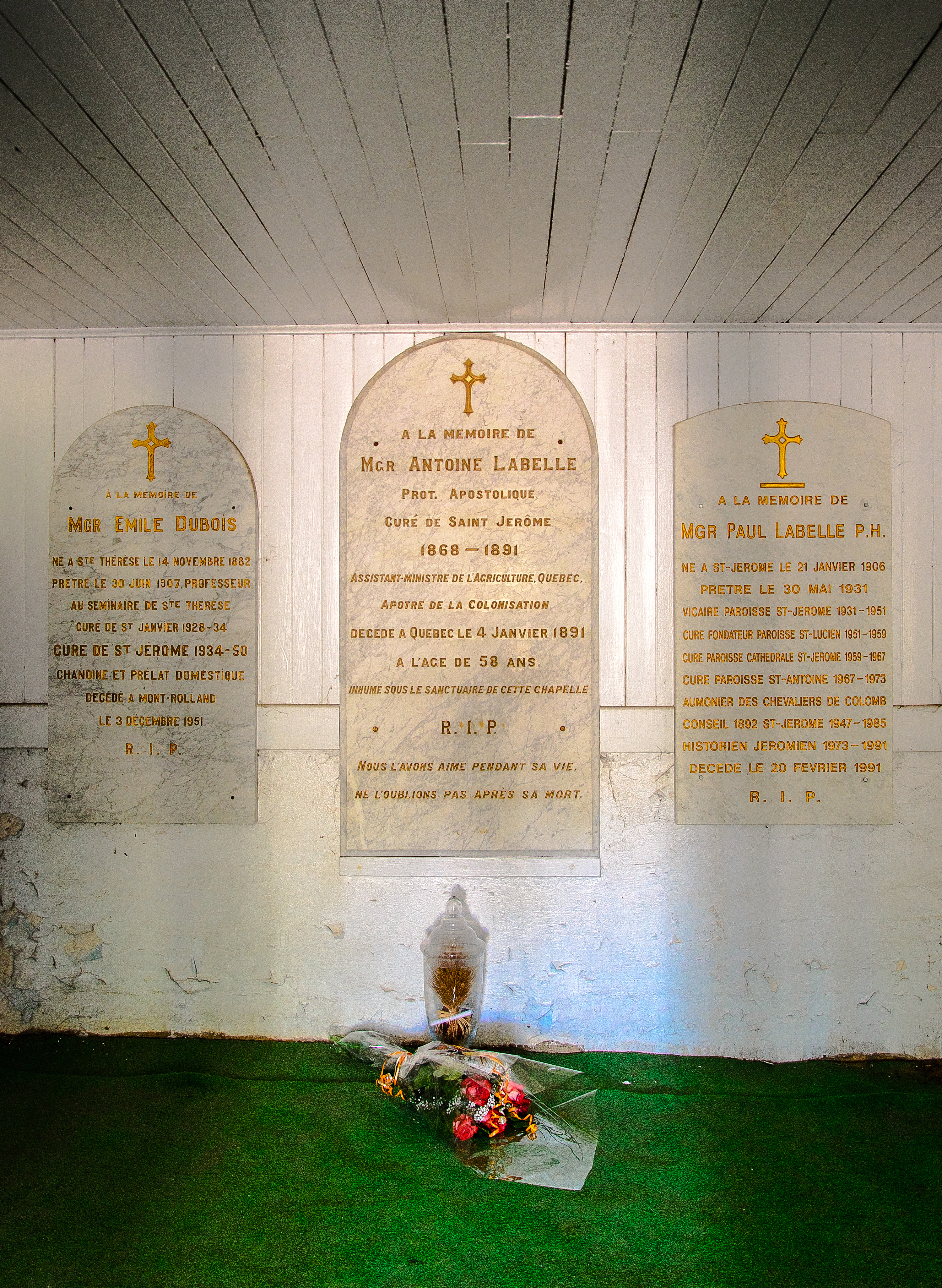 Photographie couleur d'une sépulture dans les sous-bassement d'une chapelle. Trois plaques de marbre blanc avec des écritures dorées sont accrochées au mur. Devant la plaque centrale, un bouquet de fleurs et une urne en verre sont déposés sur le sol recouvert de tapis gazon.