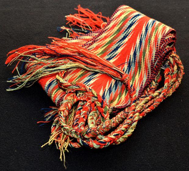 Photographie couleur d'une ceinture fléchée d'environ 20 cm de largeur et 2 m de longueur. Le tissage forme des motifs d'éclairs ou de pointe de flèche. La bande centrale de l'ouvrage, plus large, est rouge vif, les bandes subséquentes se répartissent symétriquement à droite et à gauche de la bande centrale. Aux extrémités, les fils de laine excédant le tissage forment trois longues tresses.