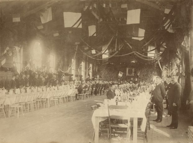 Photographie sépia d'une salle de réception plus longue que large et au plafond élevé. La salle est décorée de banderoles, de drapeaux français et de sapinage. On retrouve deux longues tables parallèles dressées pour un repas. Plusieurs hommes sont attablés, les membres d'une fanfare se tiennent debout près du mur gauche.