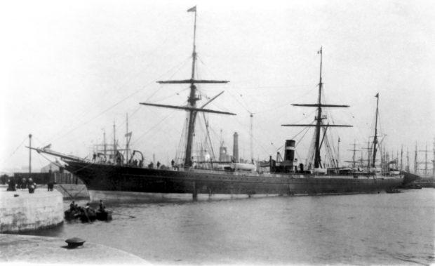 Photographie noir et blanc d'un bateau à voile et à vapeur accosté à un quai en béton dans un port. Le bateau, très grand, comprend trois mâts et une cheminée. Quelques chaloupes sont dans l'eau non loin du bateau. En arrière-plan, plusieurs mâts d'autres bateaux.