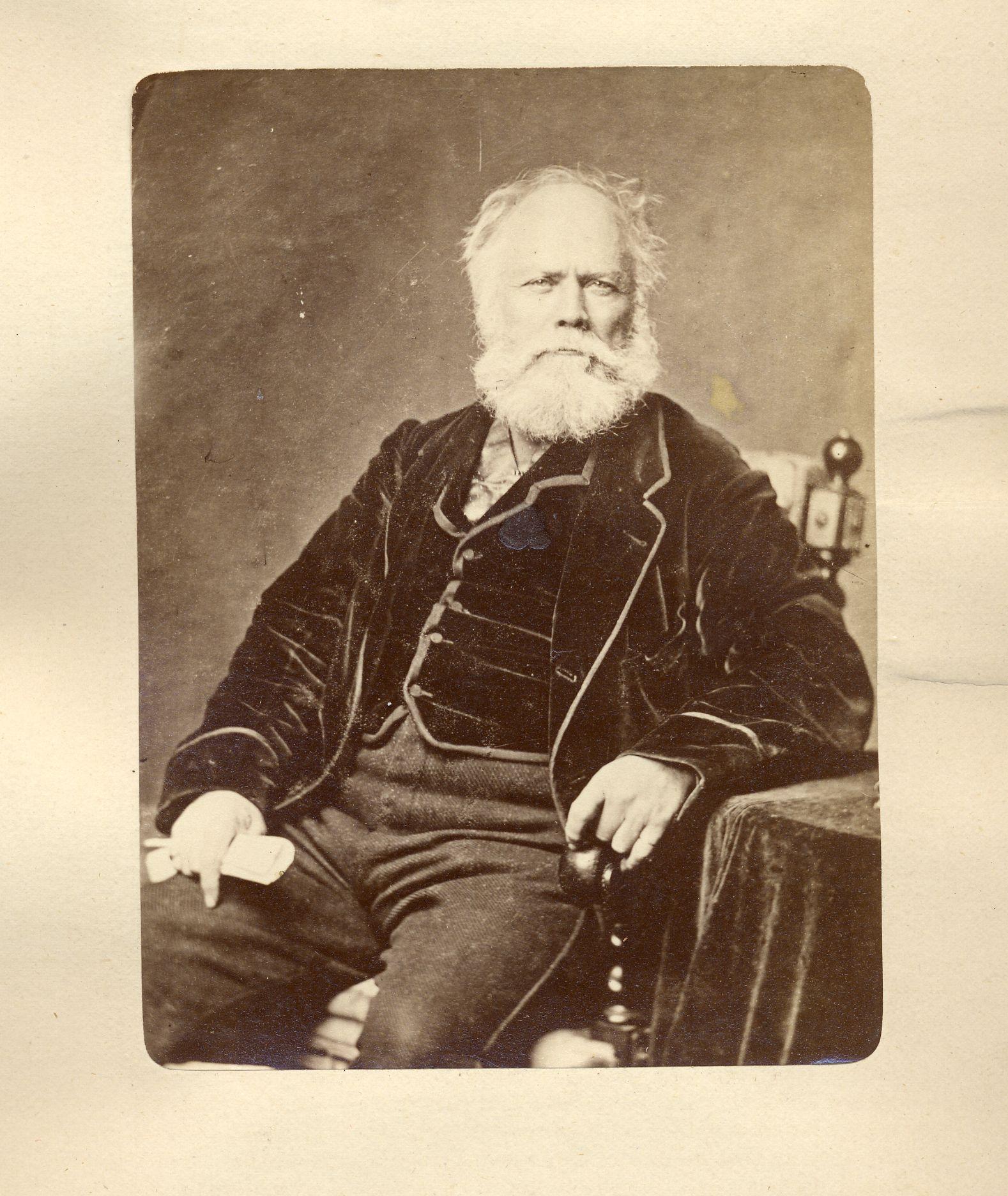 Photographie sépia d'un homme d'une soixantaine d'années assis sur une chaise. L'homme a les cheveux blancs, son front est dégarni. Il porte une barbe blanche fournie de longueur moyenne. Il est vêtu d'une veste et d'un gilet de velours foncé et d'un pantalon fabriqué dans un matériau plus léger. Un de ses bras est appuyé sur une table nappée de velours.