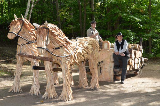 Photographie couleur montrant une sculpture réalisée par l'assemblage de bois de grève. L'œuvre de grandeur nature se trouve dans un boisé. Elle représente un traîneau rempli de billots de bois tiré par deux chevaux. Un homme sculpté dans le bois est assis à l'avant du traîneau. Deux hommes vêtus à la mode de l'époque prennent la pose sur le traîneau.