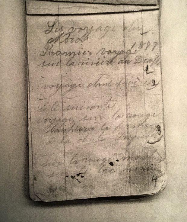 Photographie d'une page d'un carnet de notes. Il y est inscrit, à la main au crayon de plomb : « Les voyages du Nord. 1877, Premier voyage sur la rivière du Diable. » Quelques autres destinations suivent.