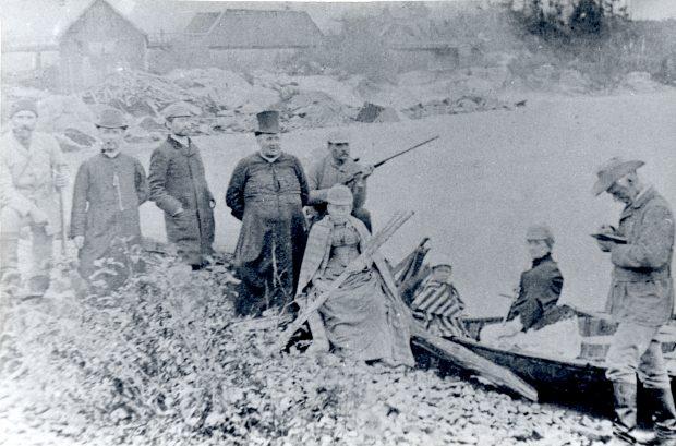 Photographie noir et blanc représentant un groupe de personnes sur le bord d'une rivière à côté d'un canot. On retrouve deux prêtres, deux femmes, un enfant, deux hommes tenant des carabines, un homme prenant des notes et un autre homme. En arrière-plan, on aperçoit un pont de bois et des bâtiments en bois.