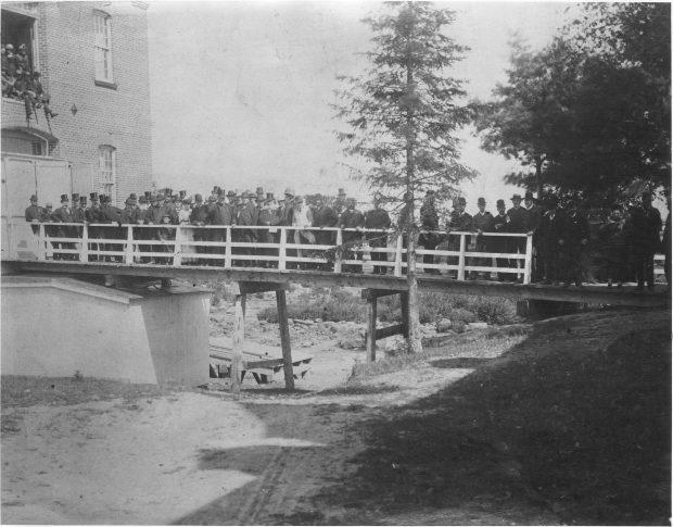 Photographie noir et blanc d'un groupe d'individus, majoritairement des hommes, debout sur une passerelle en été. La passerelle donne accès à un grand bâtiment de brique. On voit aussi des gens juchés plus haut dans une ouverture de l'usine. Plusieurs individus portent un chapeau haut de forme pour l'occasion.