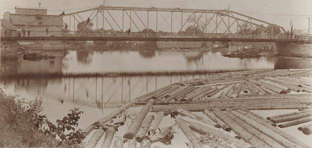 Photographie sépia d'un paysage en été dont le sujet principal est un pont de fer et une rivière. Quelques individus se tiennent sur le pont ou sont montés dans la structure. En premier plan, on aperçoit des troncs d'arbres qui flottent dans l'eau. Quelques bâtiments de bois sont en arrière-plan.