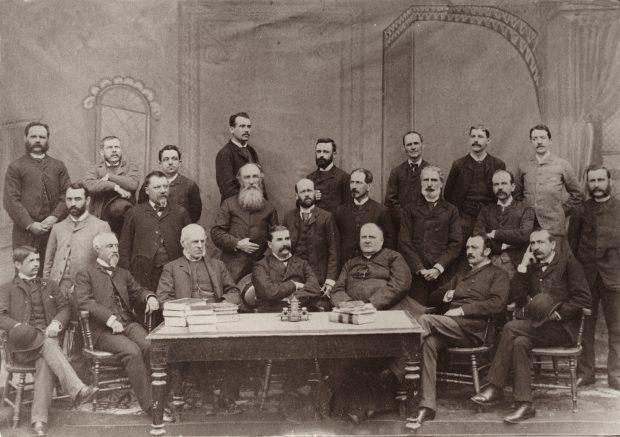 Photographie noir et blanc des vingt-trois membres du ministère de l'Agriculture et de la Colonisation le 1er septembre 1889. Seize hommes sont debout derrière un groupe de sept hommes assis sur des chaises derrière une table.