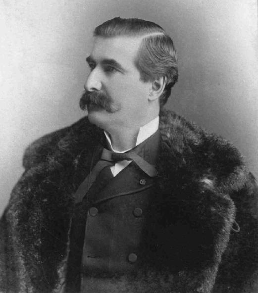 Photographie noir et blanc d'un homme dans la quarantaine. Ses cheveux sont foncés et il arbore une moustache fournie. Sous un manteau de fourrure, l'homme porte des vêtements élégants.