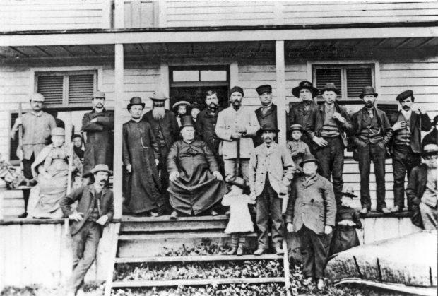 Photographie d'un groupe d'une vingtaine d'individus sur la galerie d'une maison en bois. Au centre du groupe, le curé Labelle, un homme corpulent en soutane est assis sur une chaise. À droite, sur le sol devant la galerie, un grand canot d'écorce.