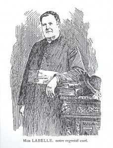 Engraving in black ink depicting a priest in his fifties, with short, curly hair. He wears a buttoned cassock, and a wide sash, symbolizing position in the Catholic hierarchy. He is standing, with his arm resting on two books that sit on a table to his left.