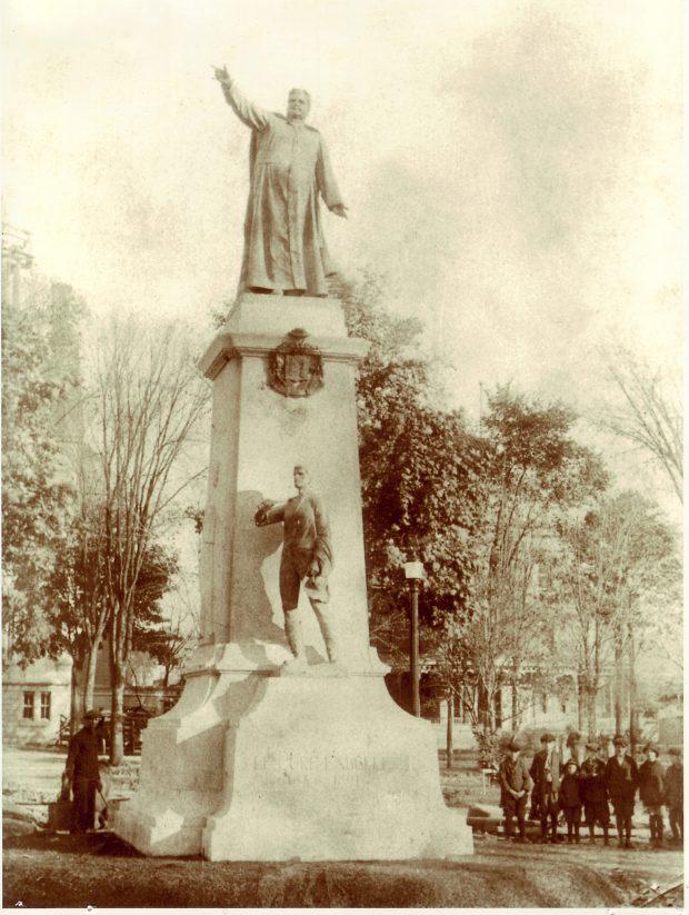 Photographie noir et blanc de la statue du curé Labelle qui pointe le doigt en direction du nord. La statue repose sur un imposant socle. Aux pieds du curé Labelle, on retrouve ses armoiries et une statue plus petite en bronze d'un paysan. Un homme et des enfants se trouvent près du socle.