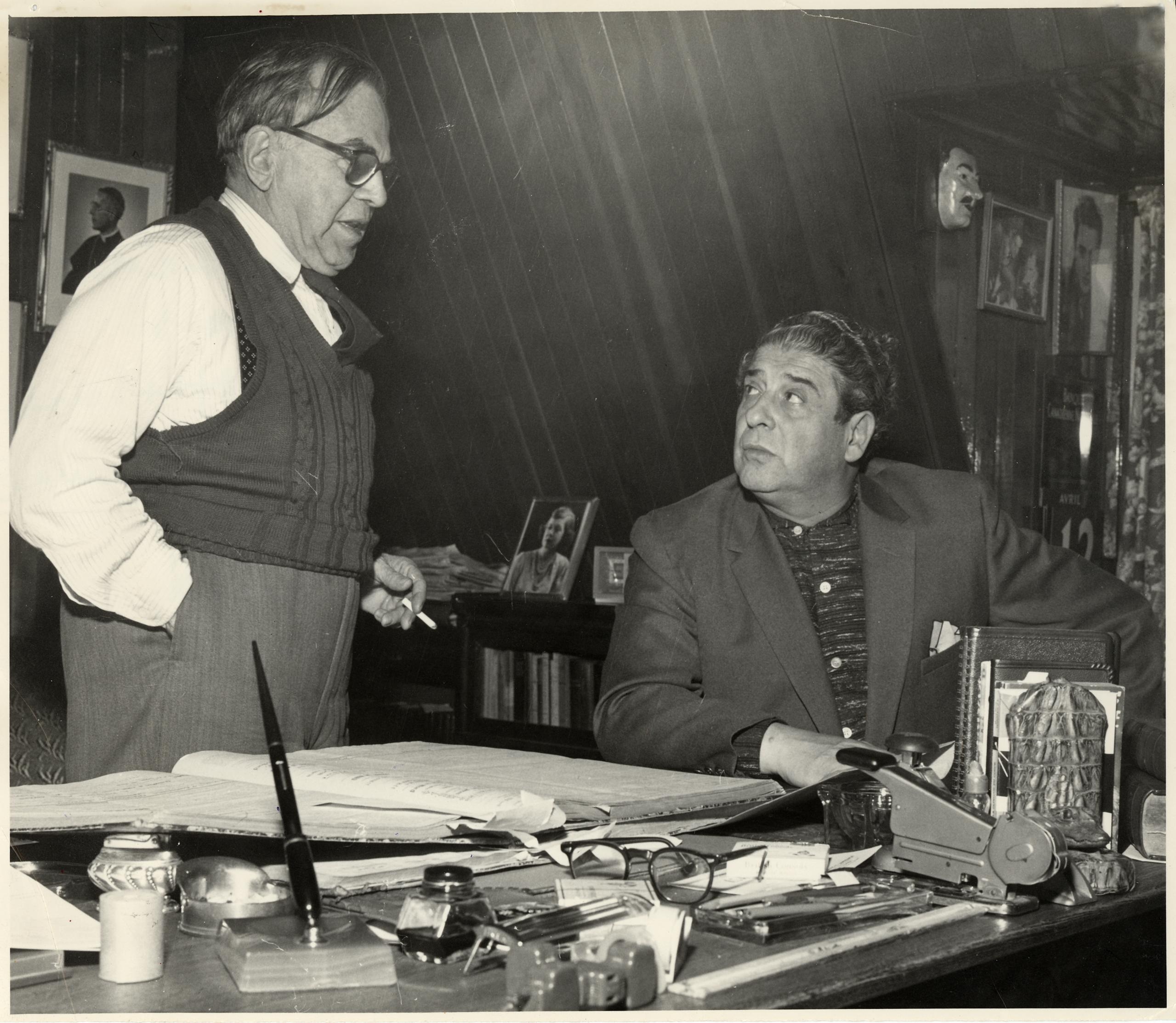 Un homme est debout près d'un bureau et discute avec un autre homme assis près de lui. Le bureau est chargé. On y trouve un grand livre ouvert, une brocheuse, des lunettes, un encrier, une plume et une multitude d'autres petits objets.