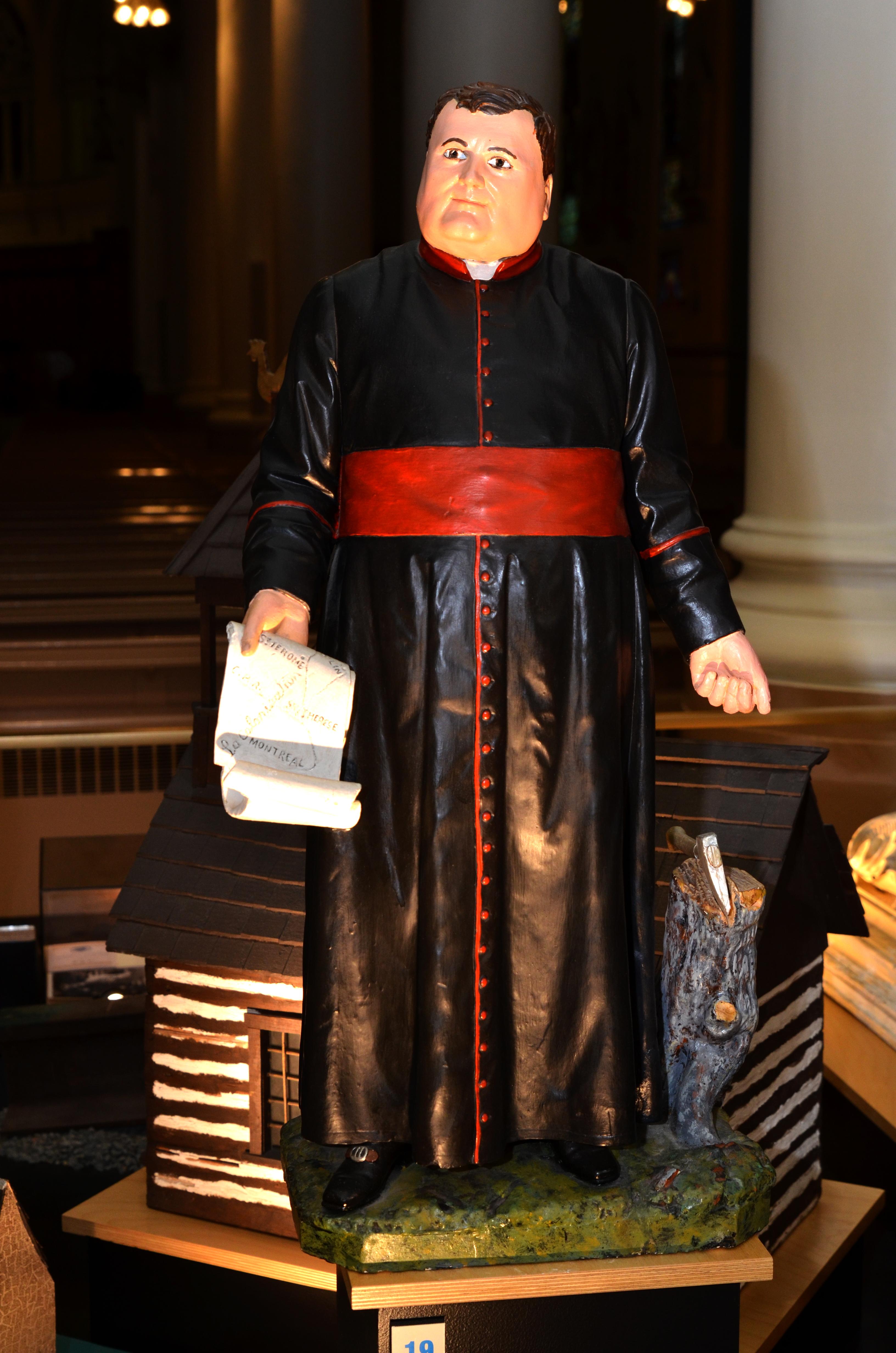 Statue de plâtre peinte. L'œuvre représente le curé Labelle tenant dans sa main droite une carte de la région des Laurentides et pointant le sol en direction d'une souche d'arbre et d'une hache de sa main gauche.