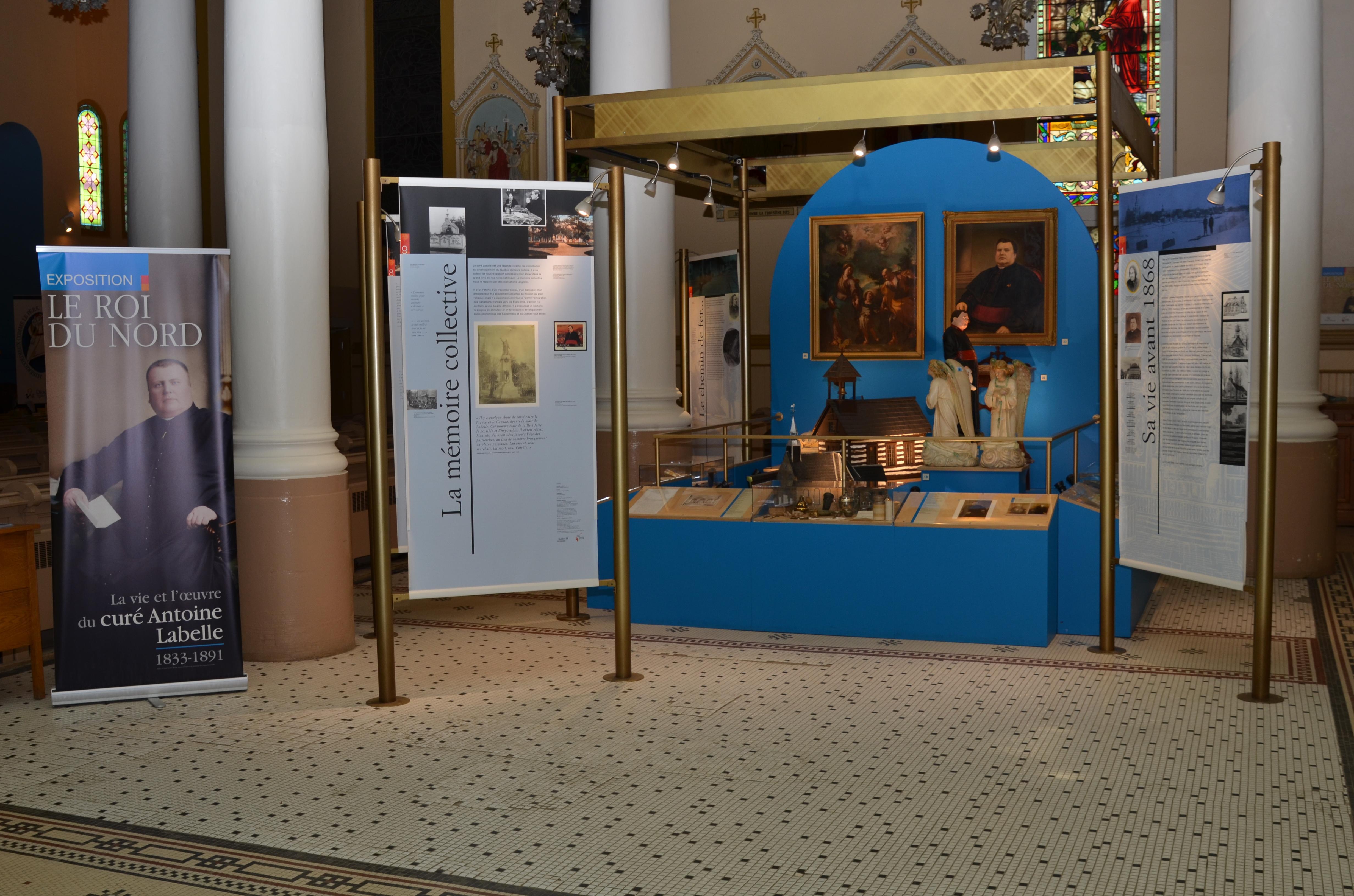 Photographie couleur de panneaux de textes et d'images d'une exposition entourant des vitrines d'objets.