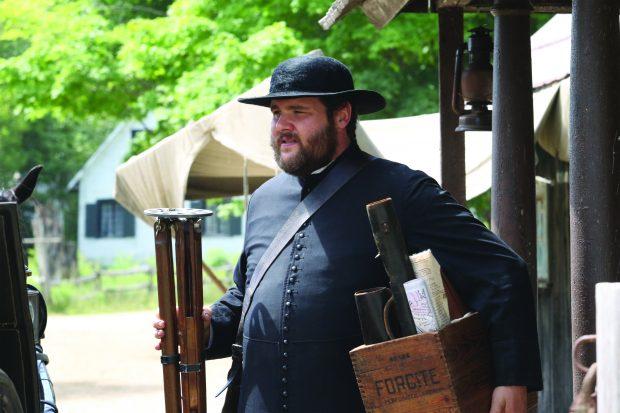 Photographie couleur d'un comédien personnifiant le curé Labelle. Vêtu de sa soutane et portant un chapeau, il porte dans ses bras une boîte de plans.