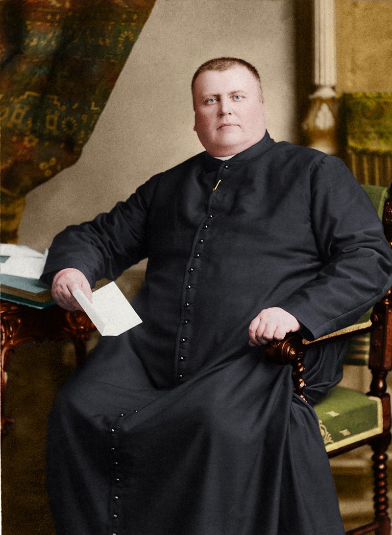 Photographie colorée du curé Labelle assis à un bureau, une lettre à la main. Son bras droit est déposé sur le bureau et le gauche sur l'accoudoir de la chaise.