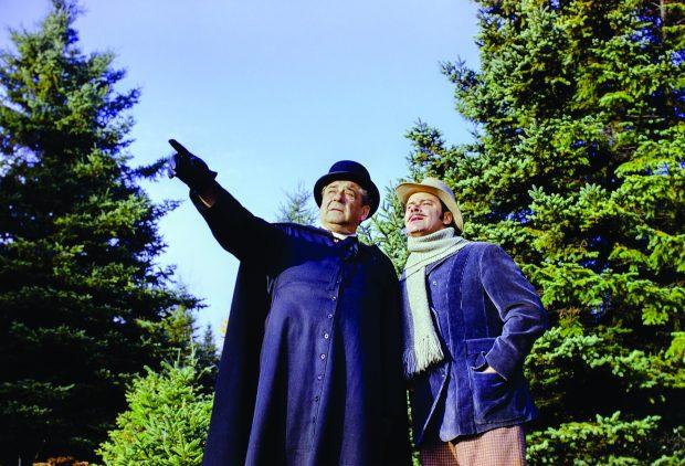 Photographie couleur de deux comédiens au milieu de la forêt. L'homme en soutane, qui représente le curé Labelle, pointe son doigt devant lui. L'homme qui l'accompagne est près de lui et regarde au loin. Il porte un manteau, un foulard et un chapeau.