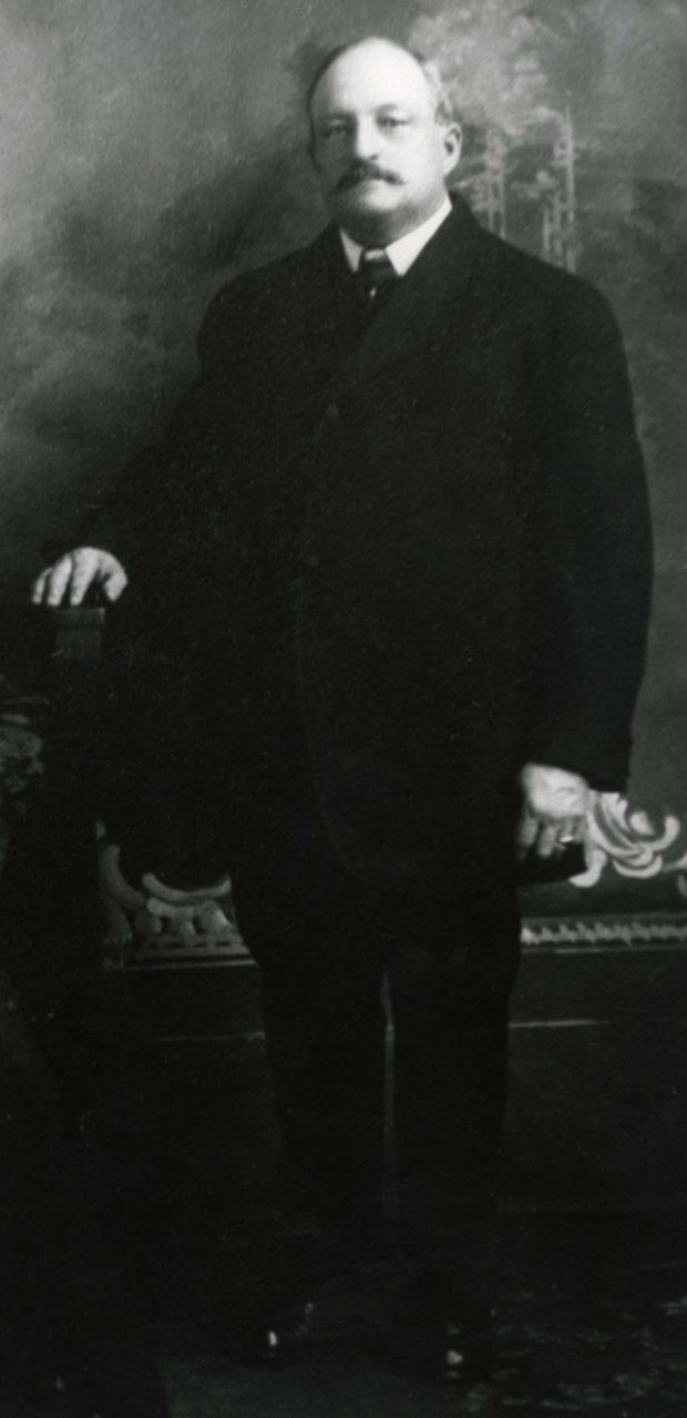 Photographie ancienne en noir et blanc d'un homme debout, habillé d'un veston noir