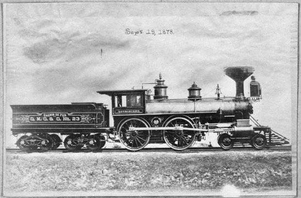 Photographie noir et blanc d'une locomotive à vapeur. La locomotive est sur les rails d'une voie ferrée. Sur la photographie, au-dessus de la locomotive, on a inscrit Sept. 19, 1878. Un petit wagon de marchandises est attaché derrière la locomotive.