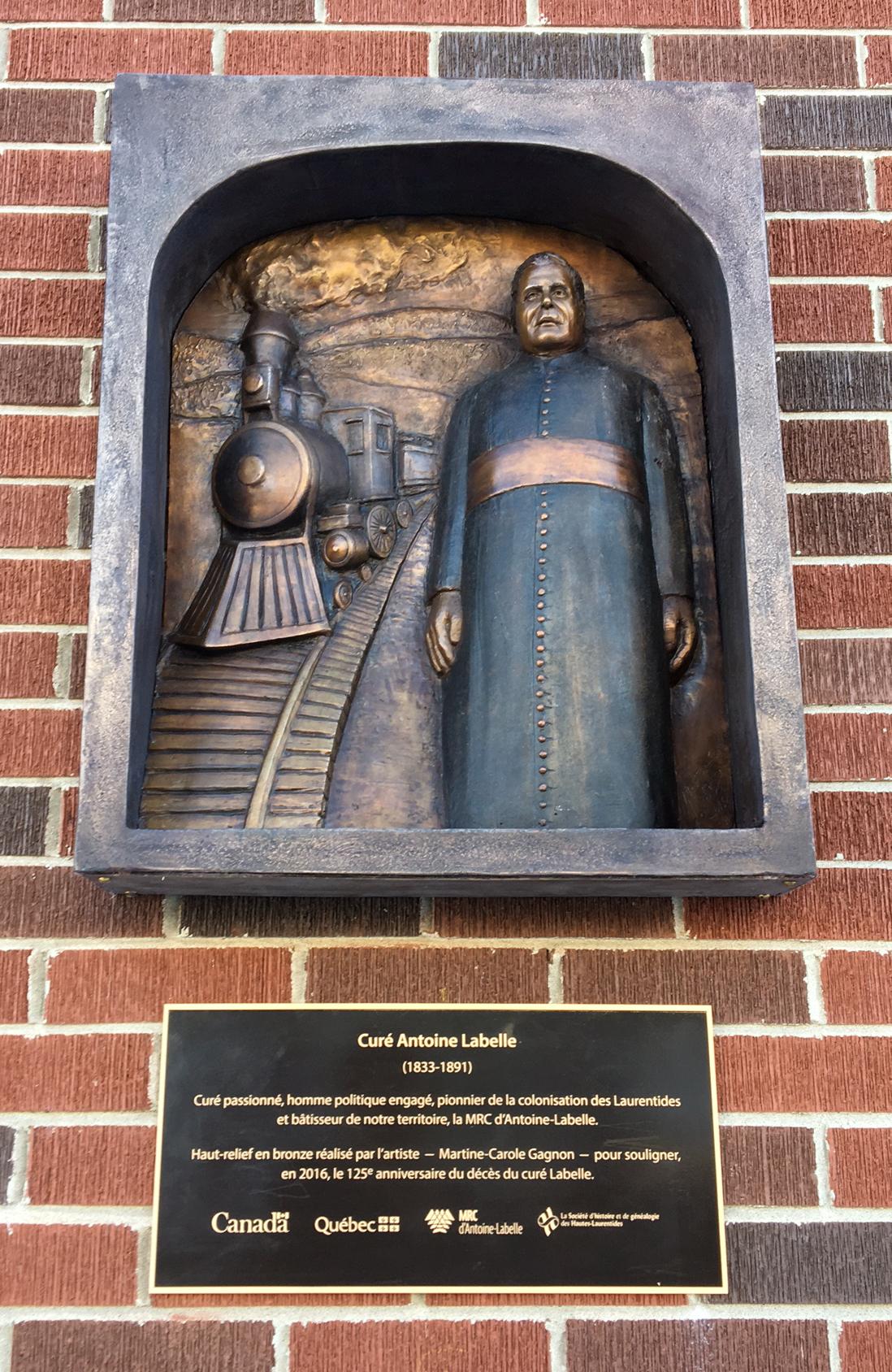 Haut-relief représentant une sculpture du curé Labelle. Dans la partie gauche, une locomotive de face et une voie ferrée et à droite, le curé Labelle debout.