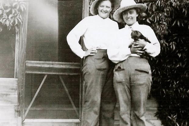 Photo en noir et blanc de deux femmes devant une porte moustiquaire. Elles portent toutes deux des pantalons de travail, des chemises blanches et de grands chapeaux. La femme de droite tient un chat dans les bras.